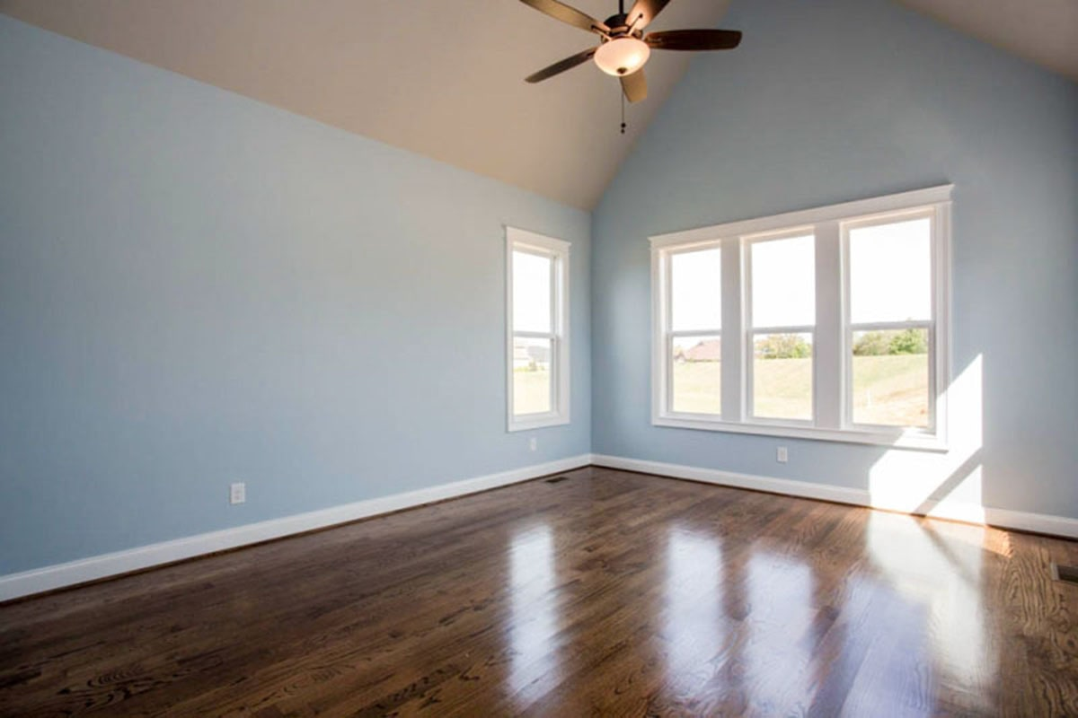 Primary bedroom with light blue walls, polished hardwood flooring, white-framed windows, and a cathedral ceiling.
