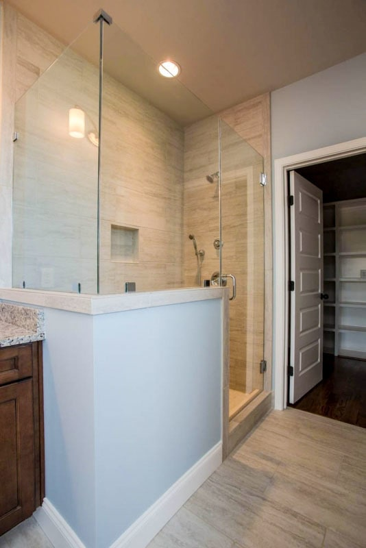 A closer look at the walk-in shower with chrome fixtures, an inset shelf, and a glass hinged door.