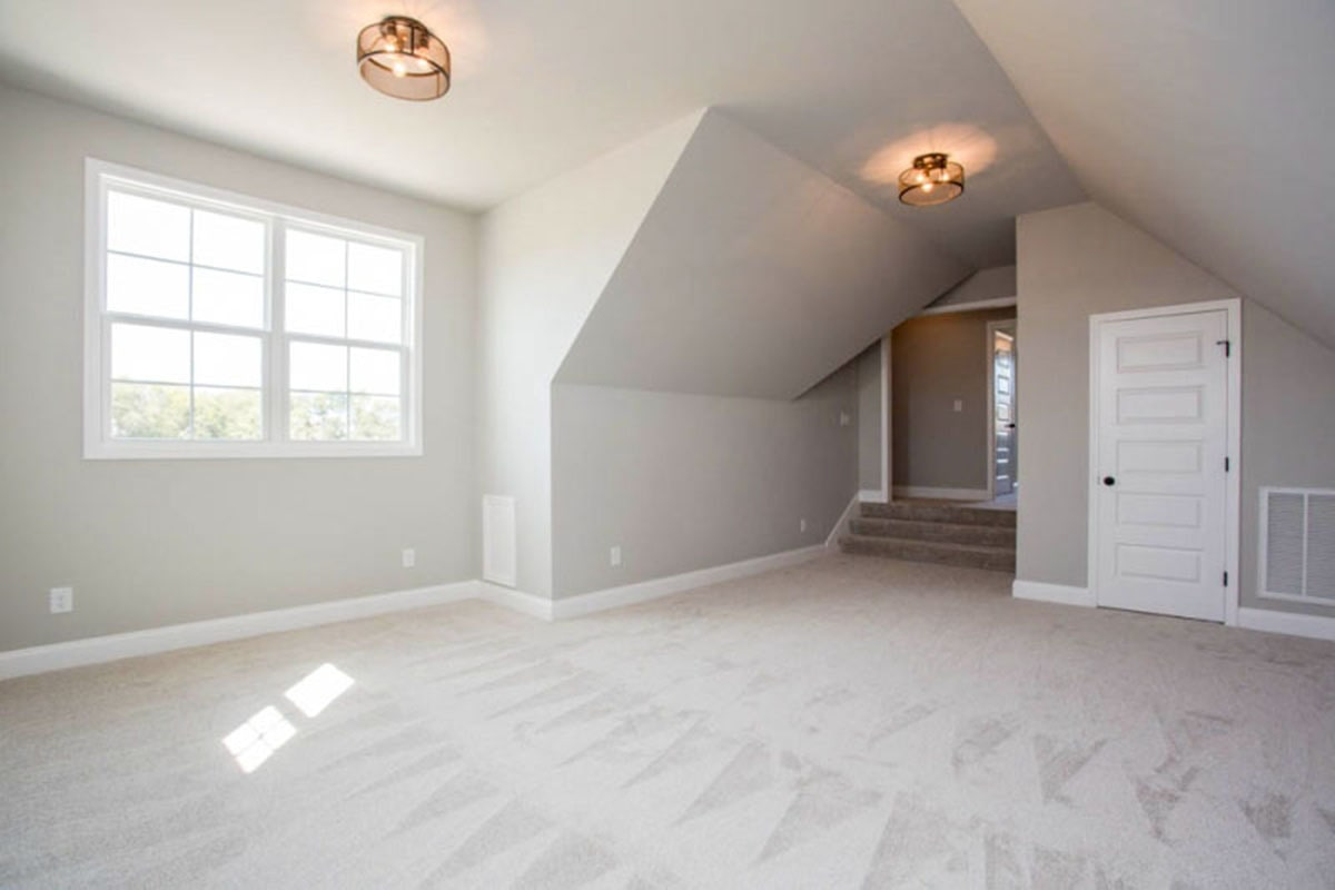 Bonus room with vaulted ceiling, carpet flooring, and a private bath.