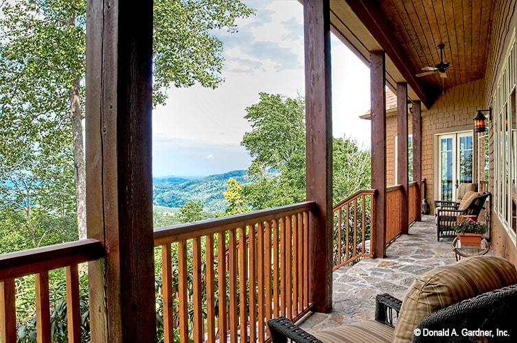The covered porch framed with wooden railings and posts overlooks a breathtaking mountain view.