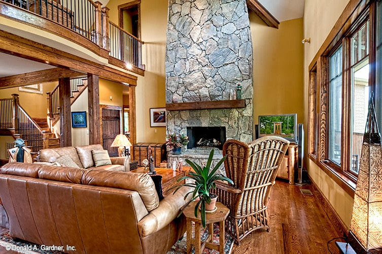The living room includes a two-story stone fireplace lined with a rustic mantel.