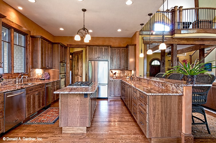 The kitchen is equipped with granite countertops, stainless steel appliances, a double bowl sink, and a cooktop island.