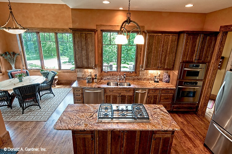 The kitchen includes an adjoining breakfast nook well-lit by a glass dome pendant.