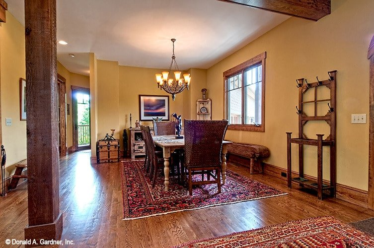 The formal dining room offers a wooden bench and a rectangular dining set paired with wicker chairs.