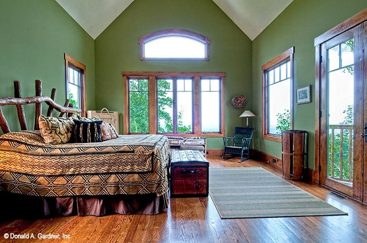Primary bedroom with green walls, a cathedral ceiling, and wooden furnishings.