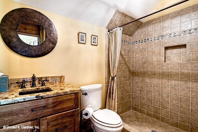 Bathroom equipped with a sink vanity, a toilet, and a walk-in shower.