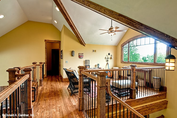 The balcony loft is filled with cushioned chairs, wooden tables, and an arched window.