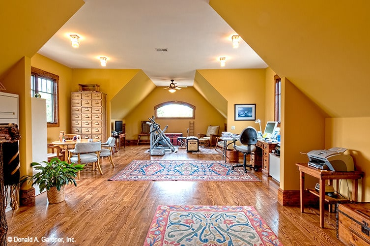 Bonus room with a vaulted ceiling, yellow walls, wooden furnishings, and hardwood flooring topped by floral rugs.