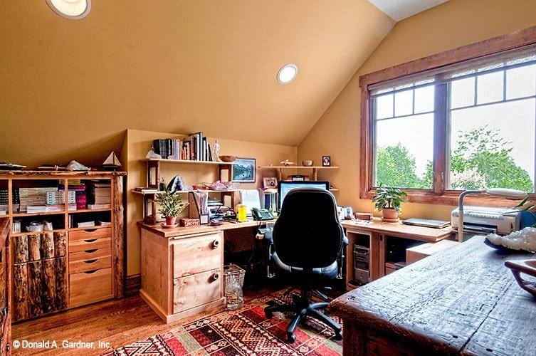 Study with a wooden desk, swivel chair, and storage cabinets.