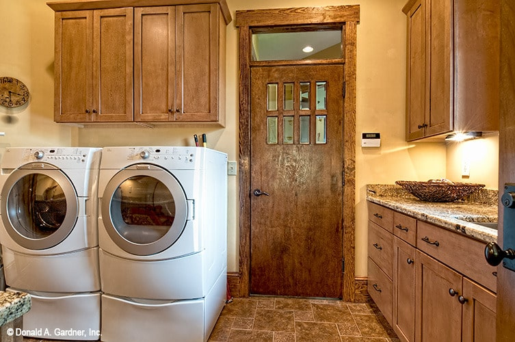 The laundry room has white front-load appliances, wooden cabinets, and a utility sink.