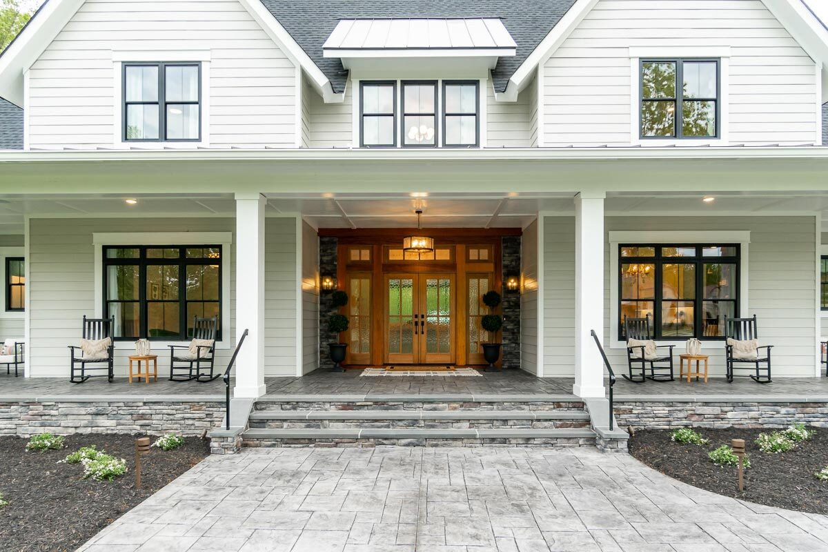 Home entry with a wide porch and a french front door surrounded by sidelights and transoms.