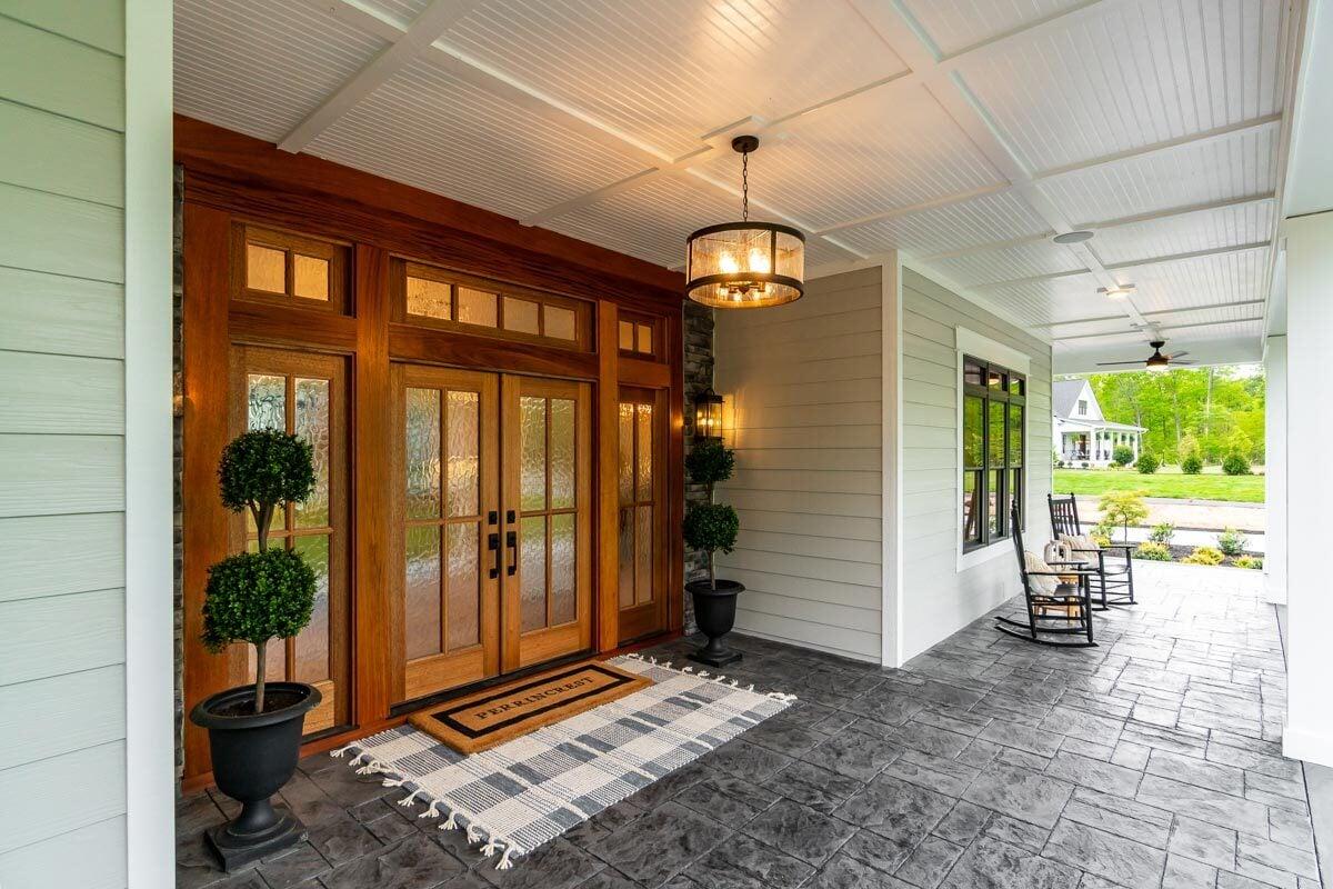 A glass drum pendant illuminates the main entrance of the house.