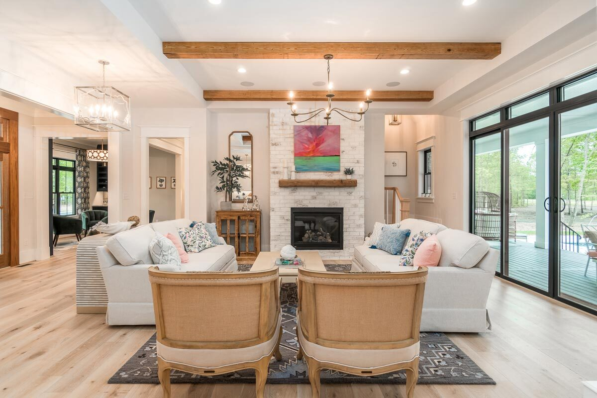 The living room has cozy seats, a brick fireplace, and a beamed ceiling.