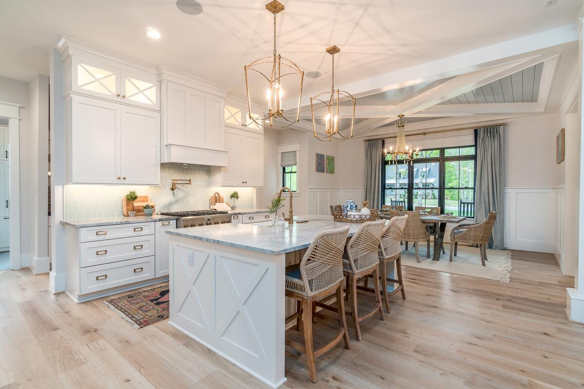 Just across the kitchen is the dining area defined by a tray ceiling. with decorative beams.