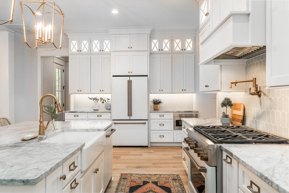 Brass hardware and fixtures accentuate the white gourmet kitchen.