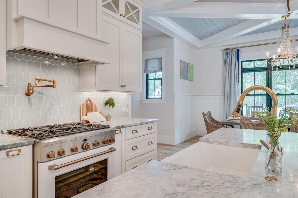 The center island is fitted with a farmhouse sink and a gooseneck faucet.
