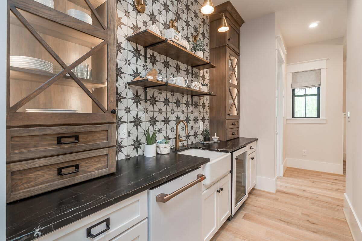 Prep kitchen with white and wooden cabinets, marble countertops, a farmhouse sink, and floating shelves fixed against an eye-catching patterned backsplash.
