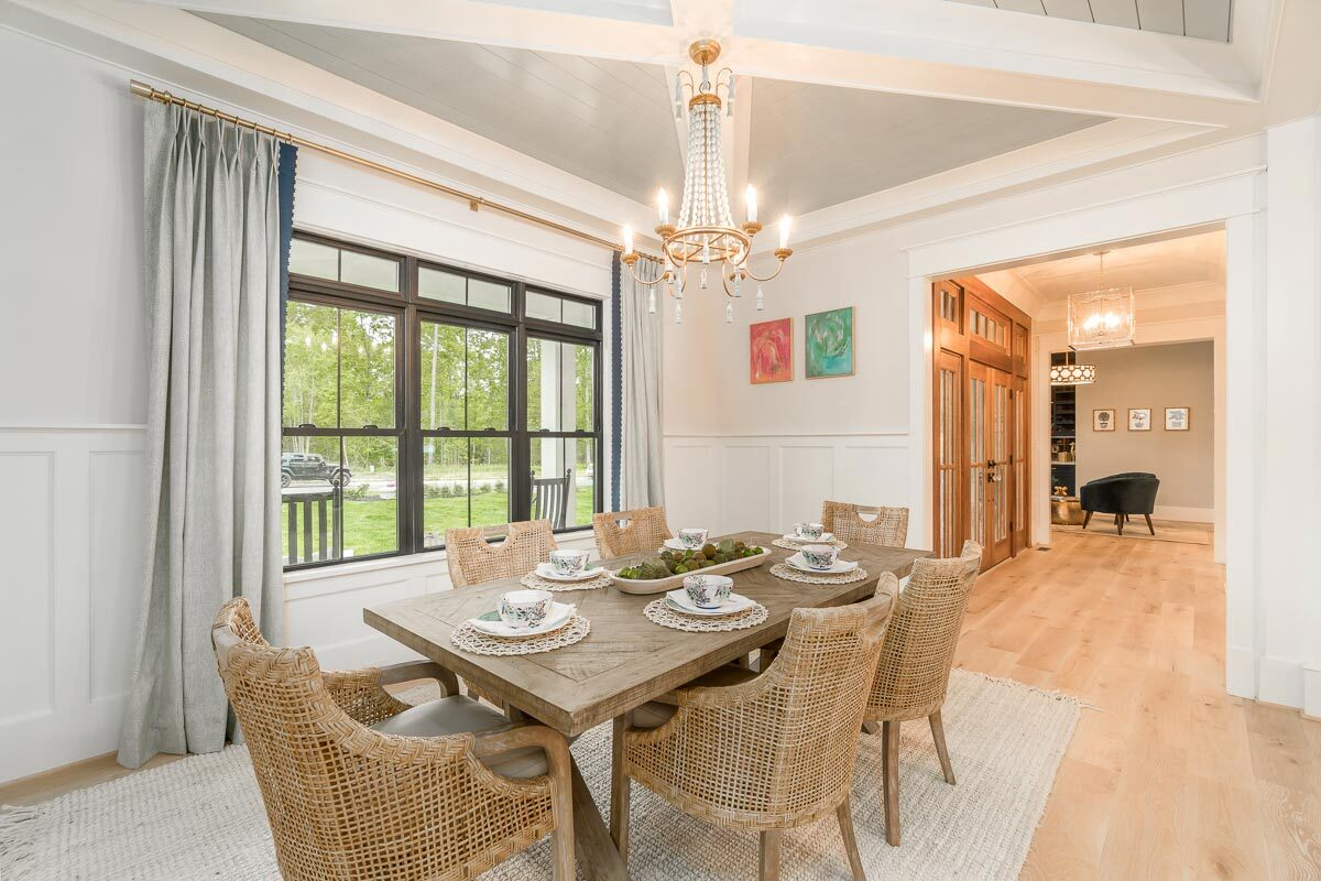 The dining room offers a beaded chandelier and a wooden dining table paired with wicker cushioned chairs.
