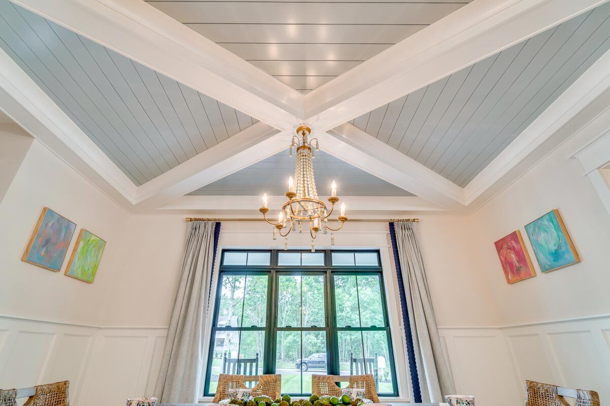 A stunning tray ceiling with decorative beams tops the dining room.