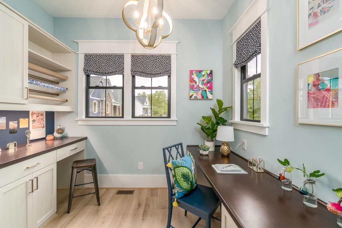 Pocket office with light blue walls, built-in desks, and light hardwood flooring.