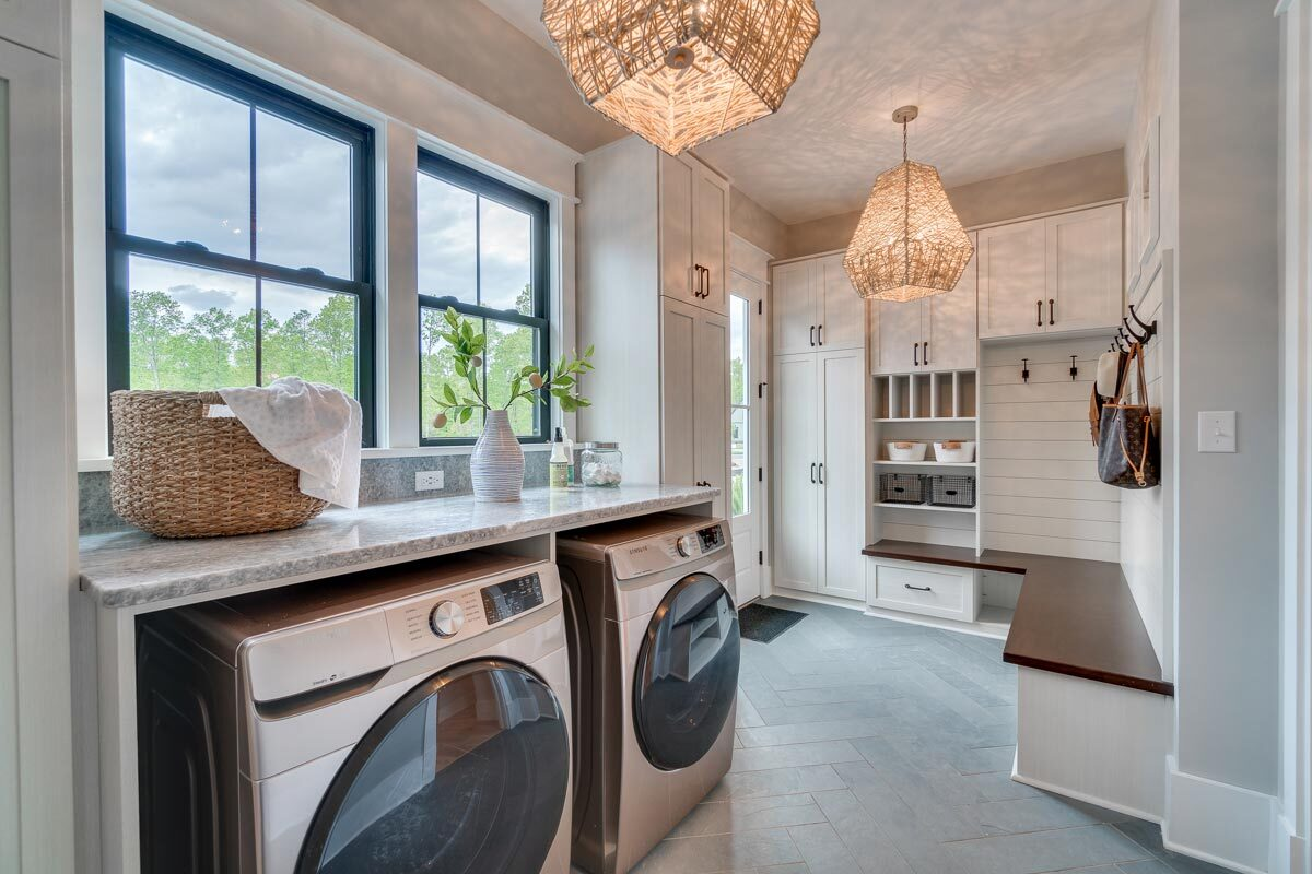 The utility room is equipped with front-load appliances, white storage cabinets, and a built-in bench.ith light blue walls, built-in desks, and light hardwood flooring.
