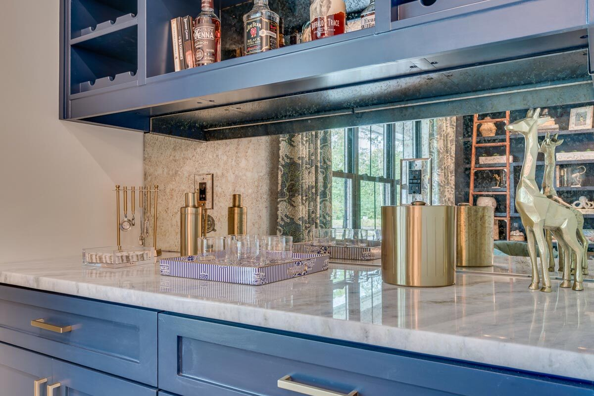 A closer look at the bar showing the marble countertop, mirrored backsplash, and blue cabinets.