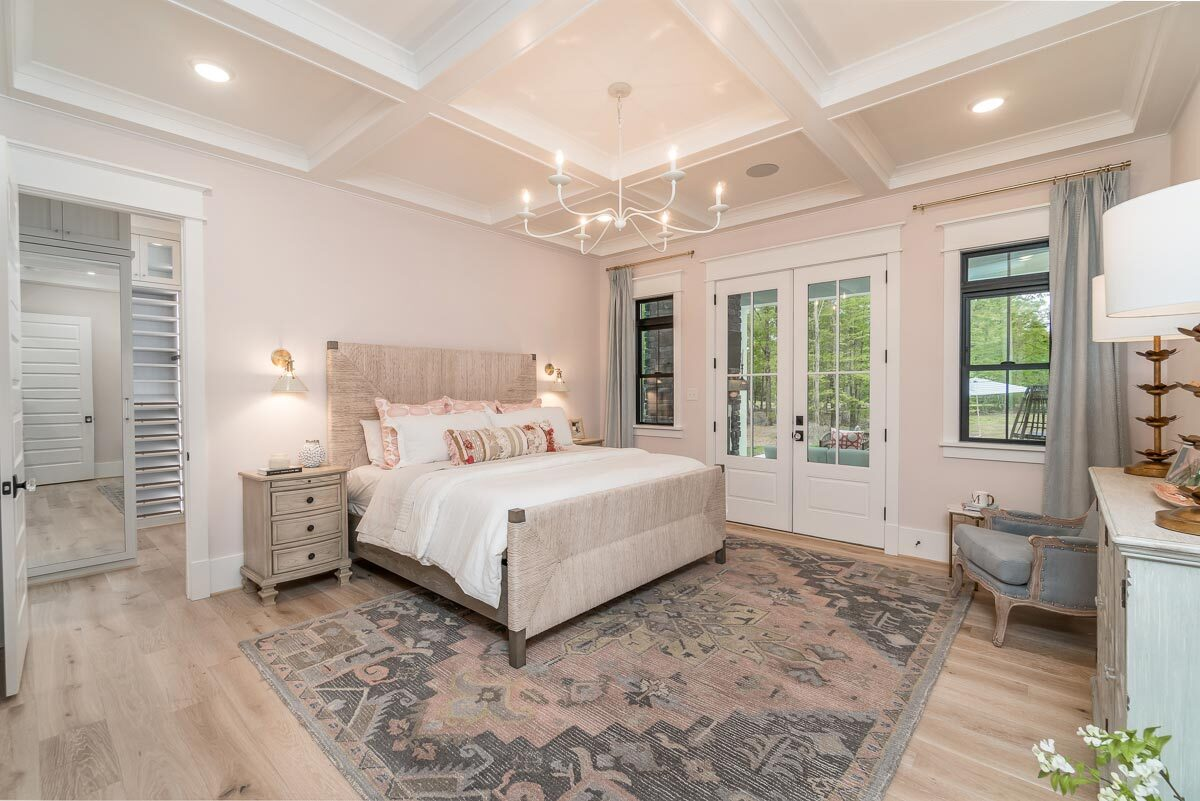 The primary bedroom features a stunning coffered ceiling, vintage area rug, and light wood furnishings that match the hardwood flooring.