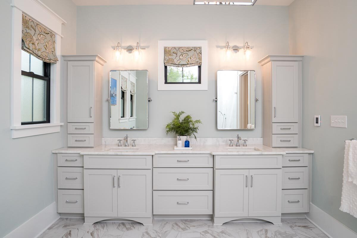 Dual sink vanity with marble countertops and a pair of mirror well-lit by glass sconces.