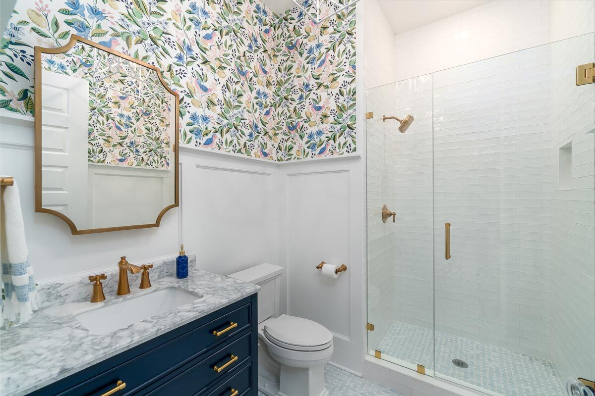 This bathroom has a nice wallpaper accent, white wainscoting, and brass fixtures.