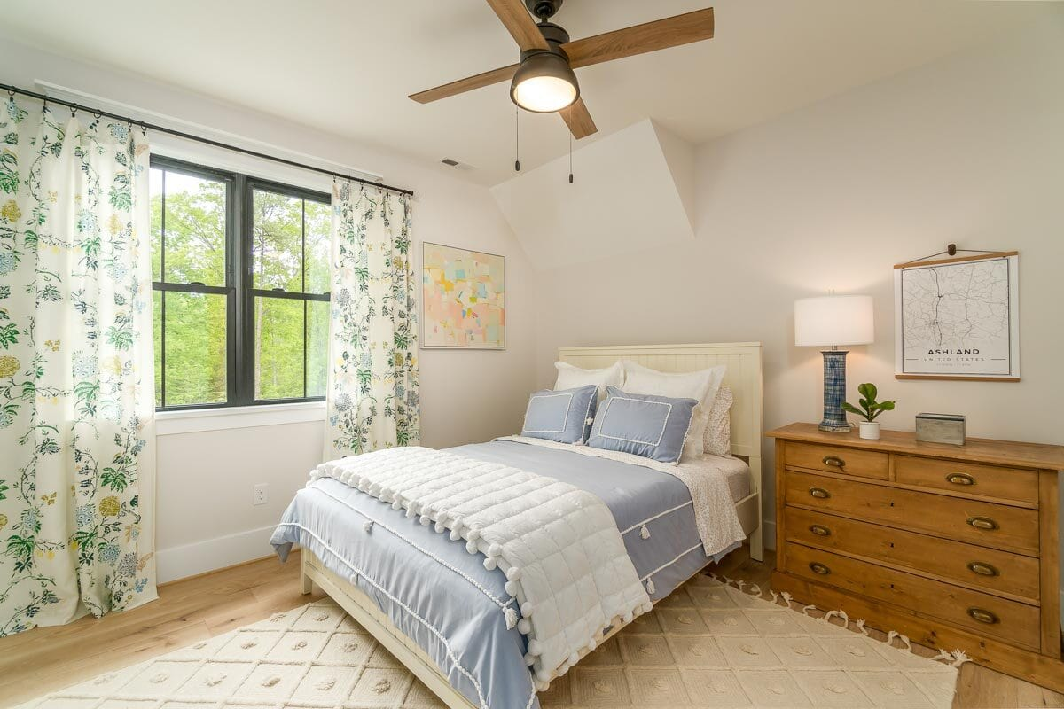 Bedroom with a white bed, wooden dresser, and a tasseled area rug.