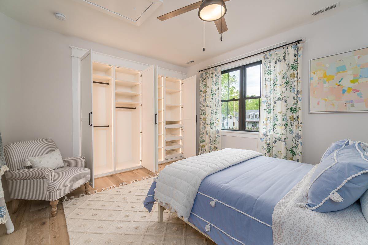 The bedroom includes a built-in wardrobe and a striped armchair.