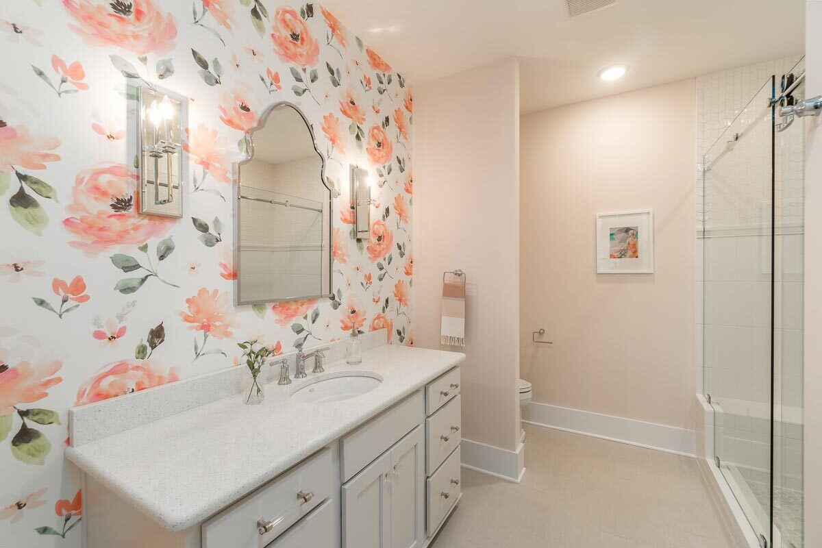 Bathroom with a large vanity, a walk-in shower, and a toilet area concealed in a cream wall.