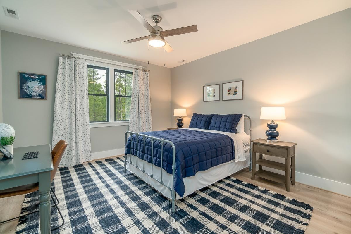 Another bedroom with gray walls, a metal bed, and a checkered area rug.