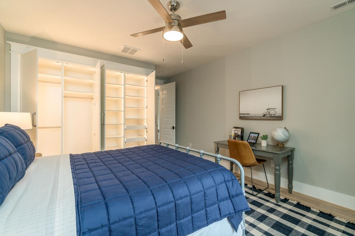 It also includes a built-in wardrobe and a gray desk with a contemporary chair.
