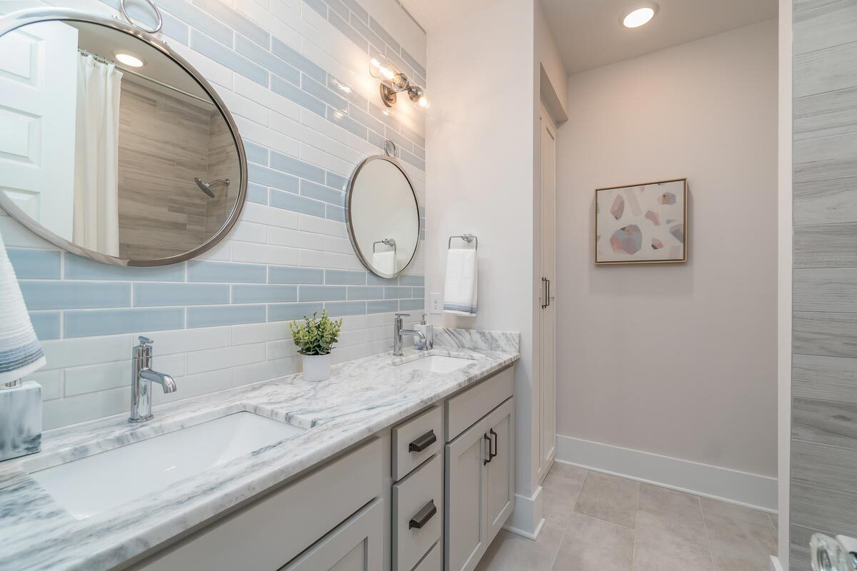 This bathroom features a white and blue subway tile backsplash mounted with round mirrors.This bathroom features a white and blue subway tile backsplash mounted with round mirrors.