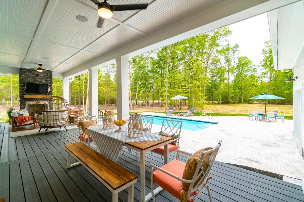 The covered porch transitions to the pool area with tall trees in the background for privacy.