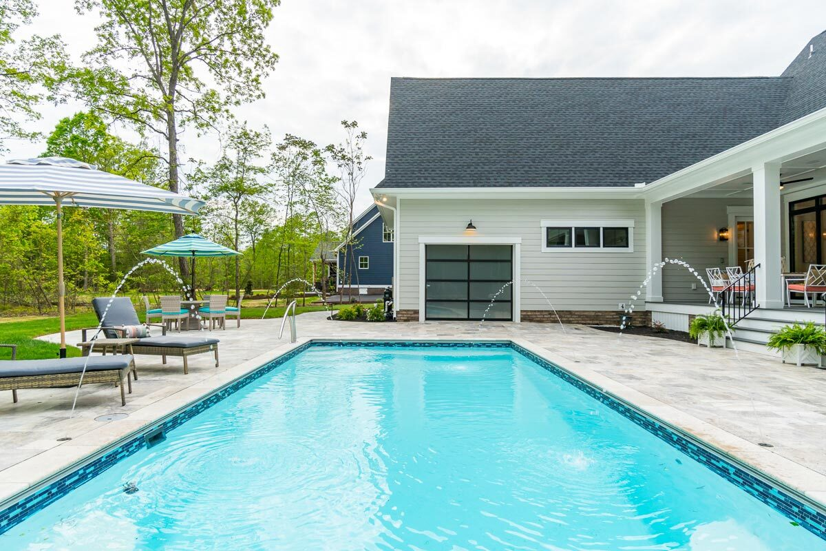 The swimming pool has water features that add to the home's appeal.