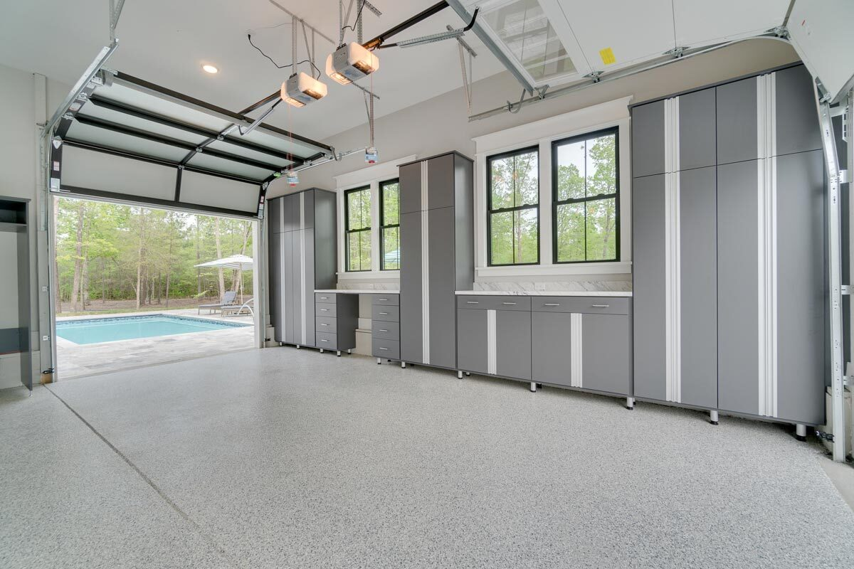 Across the pool is the garage with gray cabinets and marble counters.