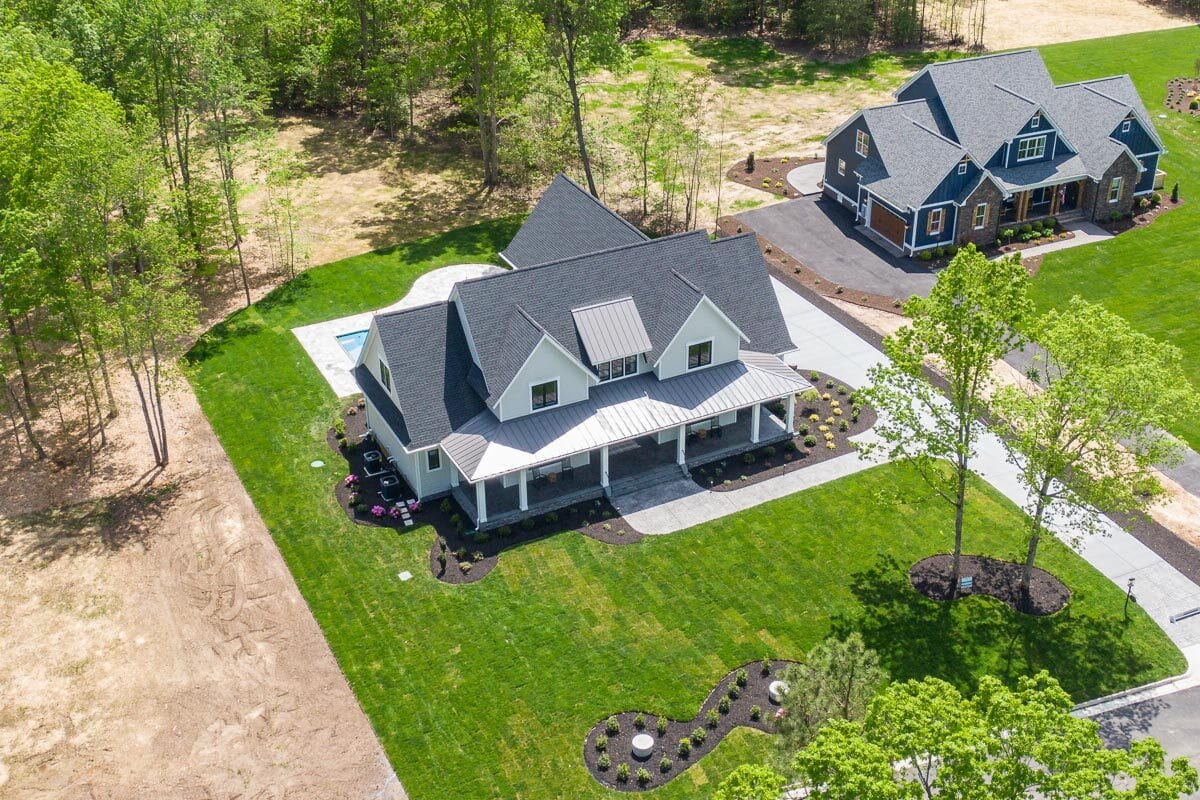 Aerial view of the modern farmhouse showing the surrounding green lawn.