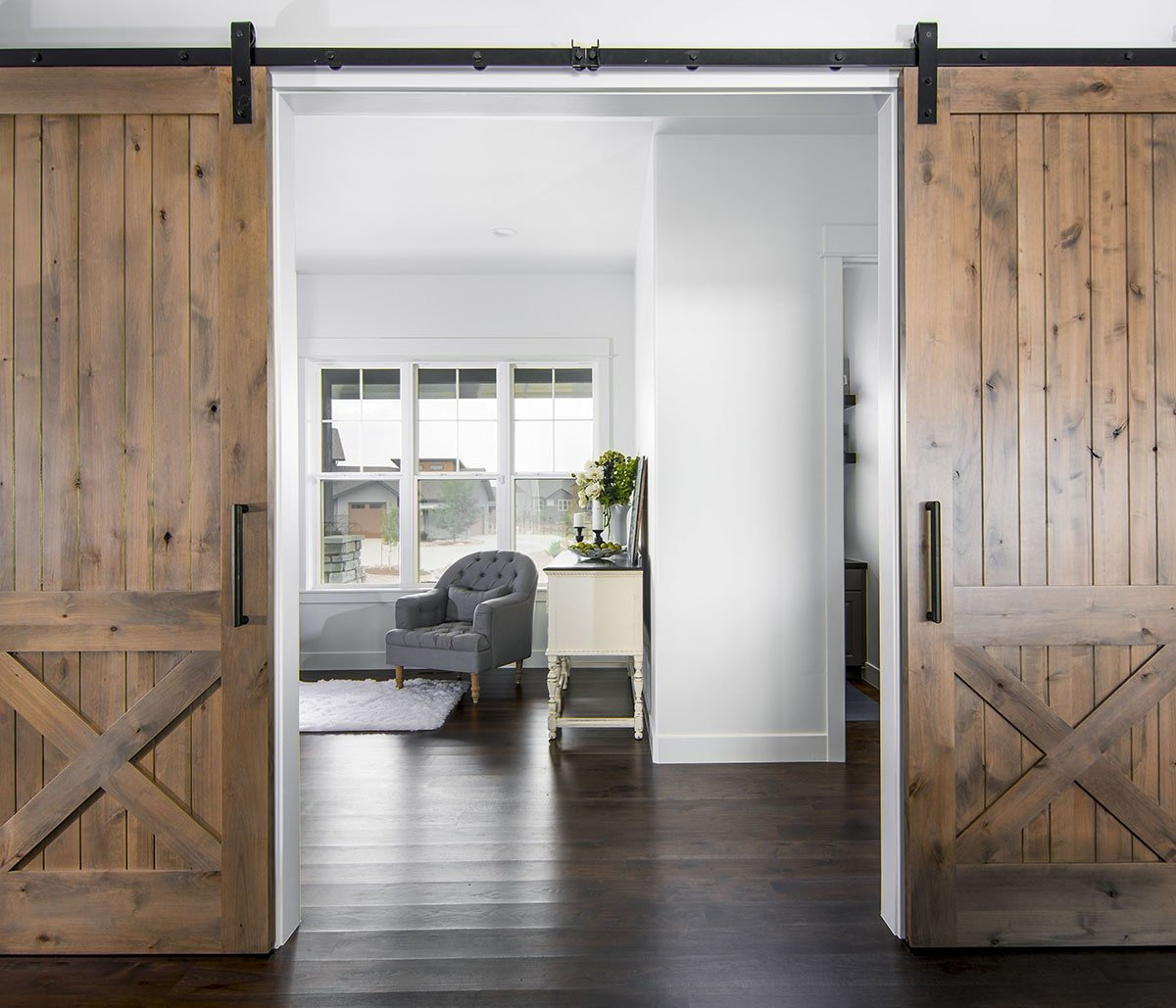 Two sets of sliding barn doors open to a quiet den.