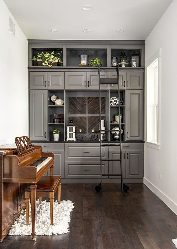 The den has an upright piano and a gray built-in cabinet with a sliding ladder.