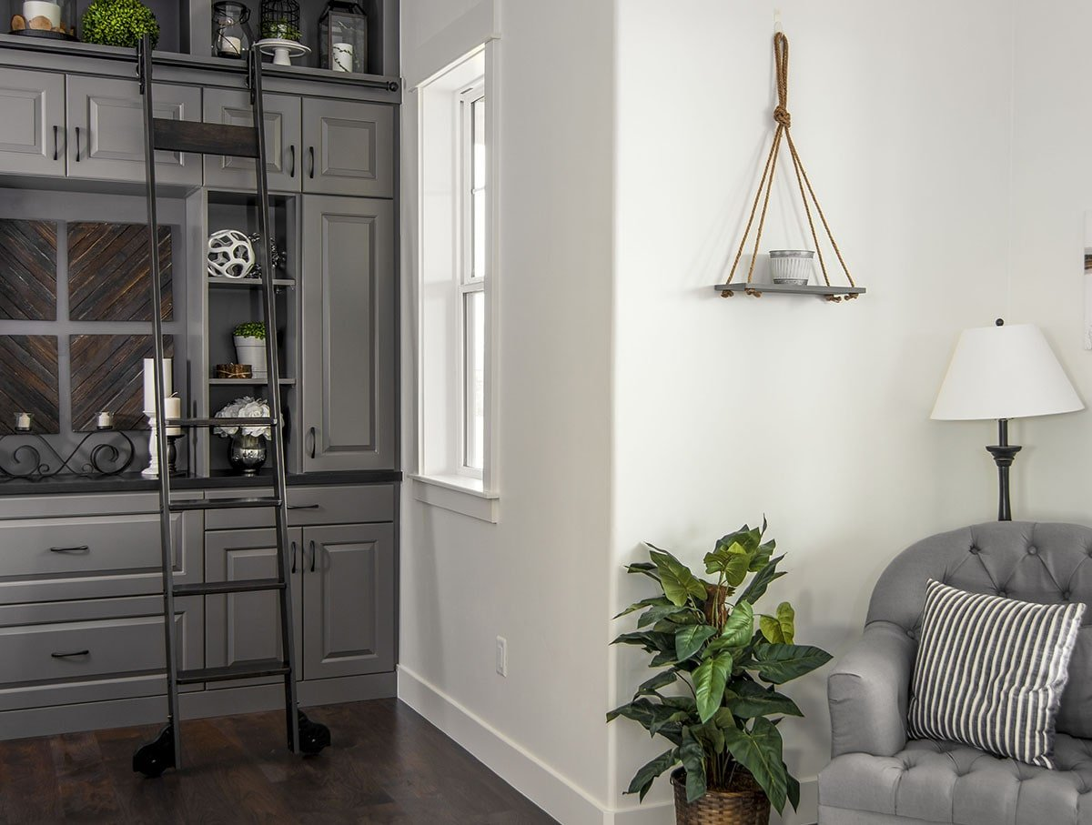 The sitting area includes a gray tufted armchair well-lit by a traditional floor lamp.