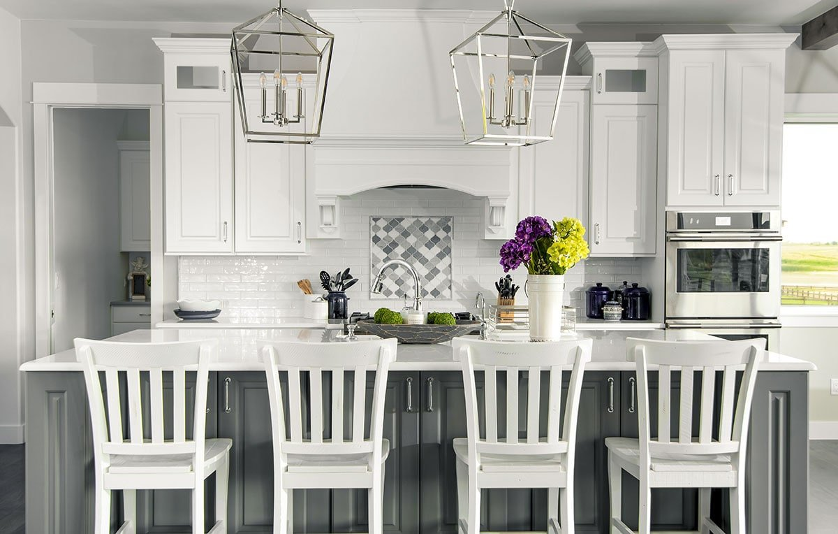 Kitchen with white cabinetry, stainless steel appliances, a large breakfast island, and a couple of chrome pendants.