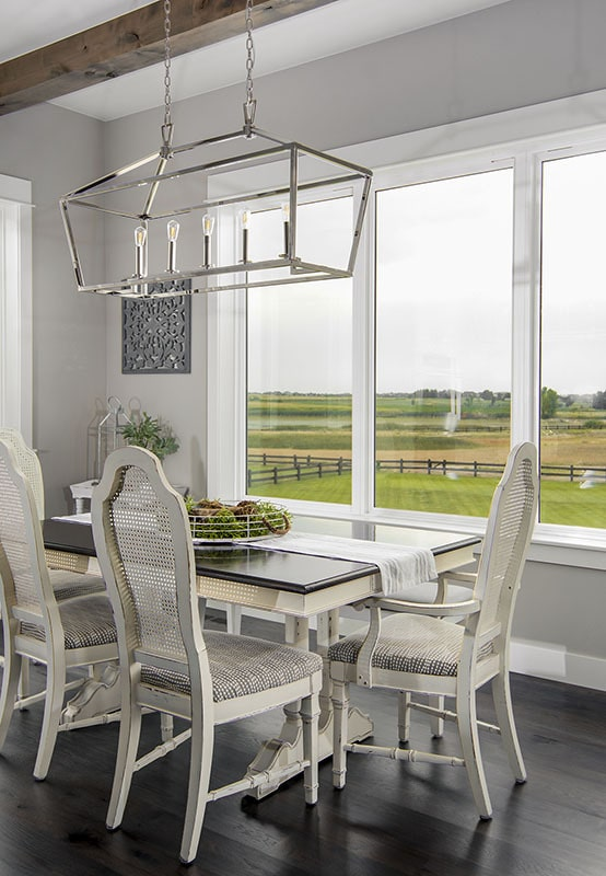 The dining area has a rectangular dining set and a trio of windows overlooking the expansive surrounding.