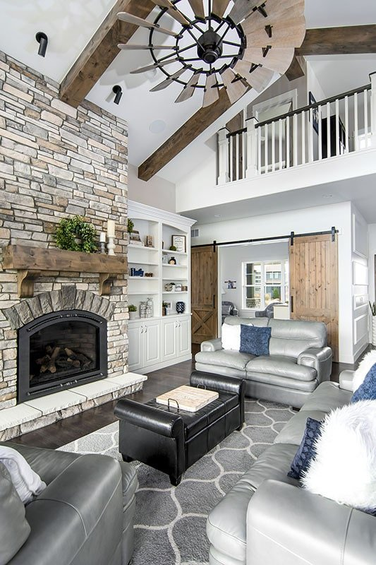 The living room has a soaring vaulted ceiling, a stone fireplace, gray seats, and white built-ins.