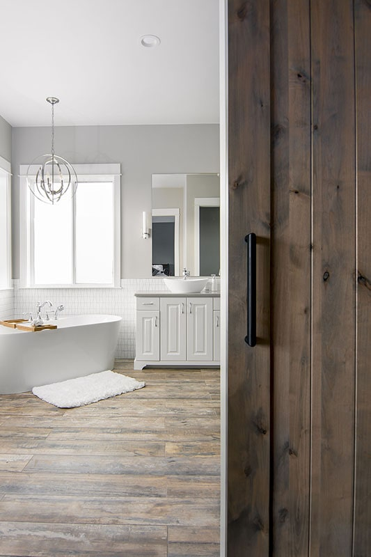 A sliding barn door opens to the primary bath with natural hardwood flooring.