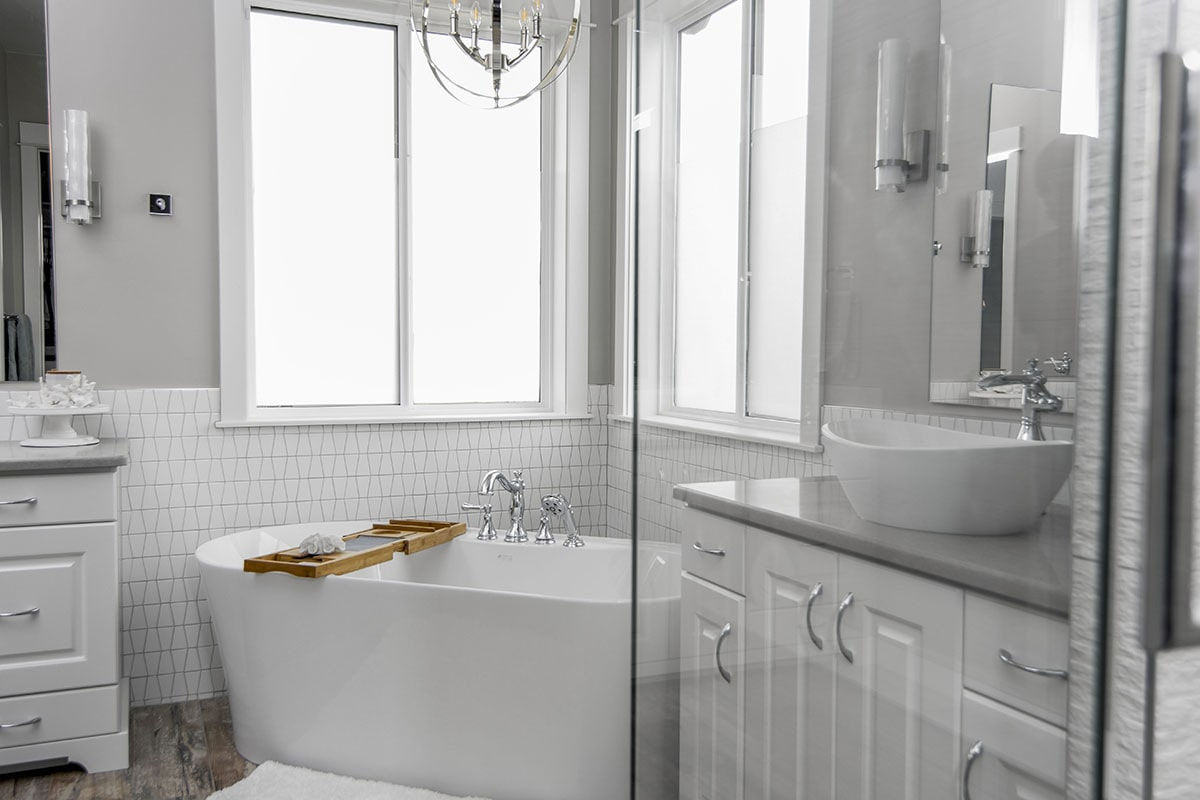 The primary bathroom is equipped with a walk-in shower, double vanities, and a freestanding tub situated in the corner.