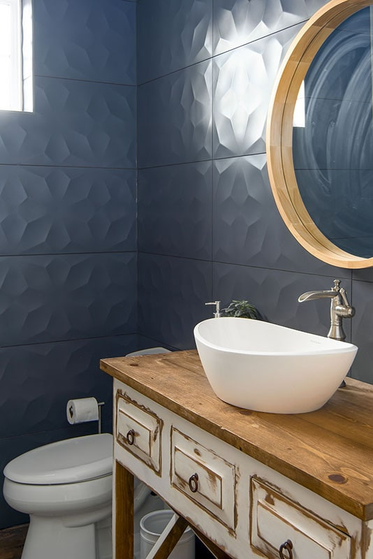 Powder room with blue textured tiled walls, a toilet, and a vessel sink vanity paired with a round mirror.
