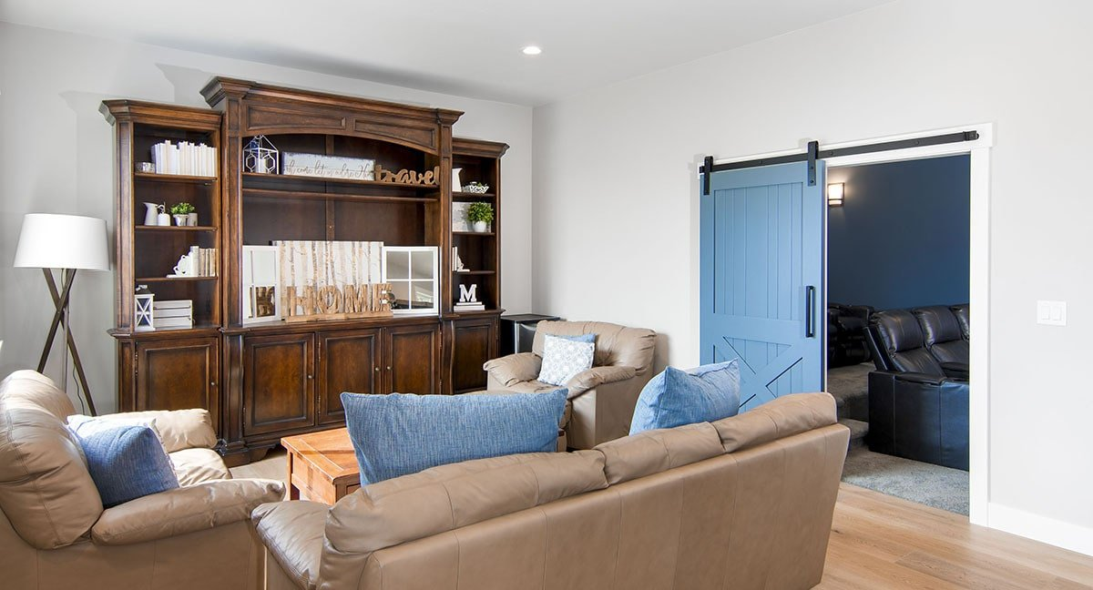 Recreation room with leather seats, a wooden cabinet, and a blue barn door that slides open to the home theater.