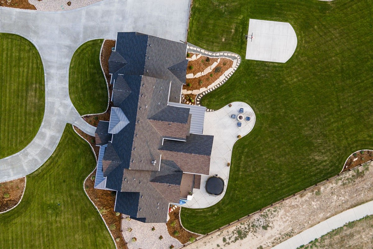Bird's eye view showing the hipped rooflines and the surrounding lush lawn.